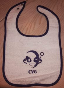 "white bib with purple border. Winking Connie printed in purple in the middle of the bib. Says ""CVG"" under Connie."
