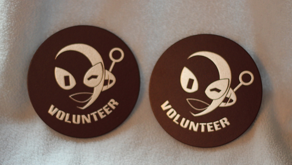"""brown round leather coasters with winking connie heads and the word """"volunteer"""" printed on them"""