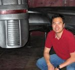 photo of Eric Chu crouching next to a model of a cylon ship